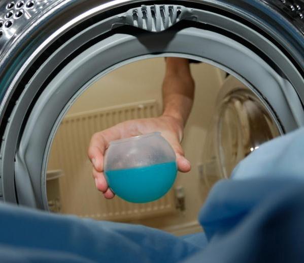 Ruka dávkující prášek do pračky