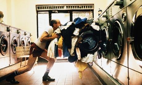 Muž v trenýrkách souká prádlo do pračky